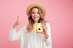 Jovem mulher bonita que guarda a câmera que mostra os polegares acima fotos de stock