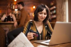 Jovem mulher bonita que guarda o cartão de crédito e que usa o portátil para comprar em linha fotografia de stock