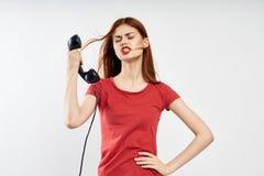 A jovem mulher bonita que guarda um receptor de telefone no branco isolou o fundo, emoções imagem de stock royalty free