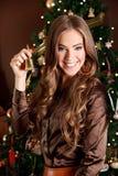 Jovem mulher bonita que guarda um sino na Noite de Natal foto de stock royalty free