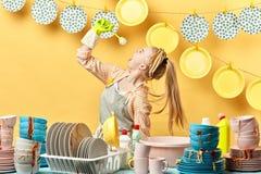 Jovem mulher bonita que guarda uma escova e que canta com ela foto de stock