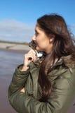 Jovem mulher bonita que huddling em seu revestimento em um dia ventoso Fotografia de Stock Royalty Free