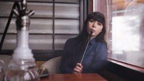 Jovem mulher bonita que inala o cachimbo de água shisha de fumo da menina no café filme