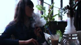 Jovem mulher bonita que inala o cachimbo de água shisha de fumo da menina no café Silhueta video estoque