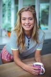 Jovem mulher bonita que inclina-se na tabela ao comer o café Foto de Stock