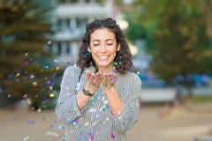 Jovem mulher bonita que joga com confetes e que tem o divertimento fora fotos de stock royalty free