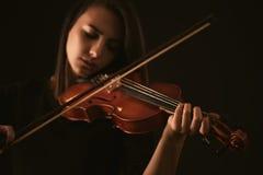 Jovem mulher bonita que joga um violino sobre o fundo preto Imagens de Stock
