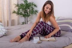 Jovem mulher bonita que lê um livro na cama com café imagem de stock royalty free
