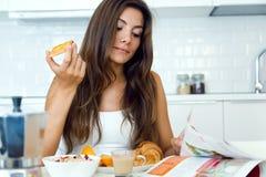 Jovem mulher bonita que lê a notícia e que aprecia o café da manhã Imagem de Stock Royalty Free