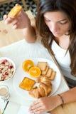 Jovem mulher bonita que lê a notícia e que aprecia o café da manhã Imagens de Stock Royalty Free