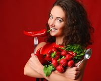 Jovem mulher bonita que levanta com a forquilha e a colher vermelhas frescas da salsa da alface de folhas do verde da pimenta de  Imagem de Stock Royalty Free