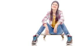 Jovem mulher bonita que levanta com um skate, assento no patim imagem de stock