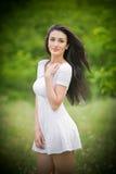 Jovem mulher bonita que levanta em um prado do verão Retrato da menina moreno atrativa com o cabelo longo que relaxa na natureza, Fotos de Stock