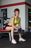 Jovem mulher bonita que levanta no fitness center imagem de stock