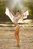 Jovem mulher bonita que levanta o sorriso com as grandes luvas no cenário do verão Menina moreno na praia no dia ensolarado Fotografia de Stock Royalty Free