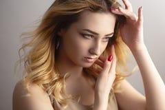 Jovem mulher bonita que levanta para uma sessão fotográfica no estúdio, cara com o cabelo encaracolado emaranhado do vento, o con imagens de stock royalty free