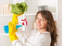 Jovem mulher bonita que limpa sua casa imagem de stock