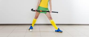 Jovem mulher bonita que mantém a vara e a bola de hóquei contra o whi foto de stock royalty free