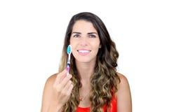 Jovem mulher bonita que mostra a escova de dentes e o sorriso Fotos de Stock Royalty Free