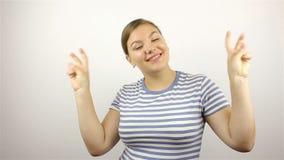 Jovem mulher bonita que mostra o sinal e o sorriso da vitória filme