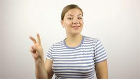 Jovem mulher bonita que mostra o sinal e o sorriso da vitória video estoque