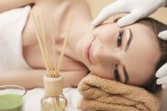 Jovem mulher bonita que obtém a massagem facial que encontra-se no sofá imagem de stock