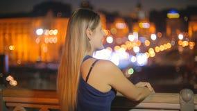 Jovem mulher bonita que olha a arquitetura da cidade iluminada na noite do telhado filme