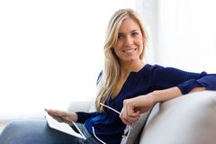 Jovem mulher bonita que olha a câmera ao usar sua tabuleta digital em casa imagem de stock