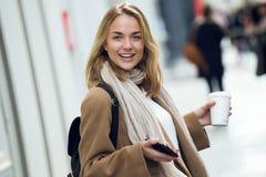 Jovem mulher bonita que olha a c?mera ao andar na rua fotografia de stock