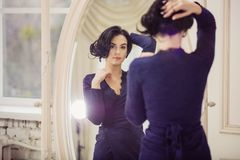 Jovem mulher bonita que olha no espelho dentro Foto de Stock