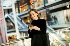 Jovem mulher bonita que olha no telefone celular no shopping Imagens de Stock Royalty Free