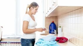 Jovem mulher bonita que olha a peúga suja na lavanderia fotografia de stock royalty free
