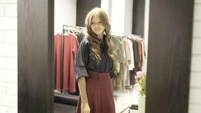 Jovem mulher bonita que olha si mesma em um espelho da loja Fotografia de Stock