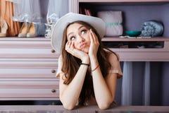 Jovem mulher bonita que pensa sobre algo em seu armário Fotos de Stock