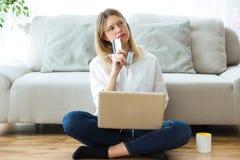 Jovem mulher bonita que pensa sobre a compra algo em linha ou não ao sentar-se no assoalho em casa imagens de stock royalty free