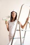 Jovem mulher bonita que pinta um apartamento Fotografia de Stock