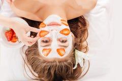 Jovem mulher bonita que recebe a máscara do fruto em uma cara no salão de beleza - dentro fotos de stock