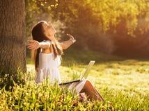 Jovem mulher bonita que relaxa na grama com portátil Fotos de Stock