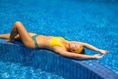 Jovem mulher bonita que relaxa na piscina fotos de stock