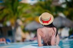 Jovem mulher bonita que relaxa na piscina Menina feliz na associação exterior no hotel de luxo fotos de stock royalty free