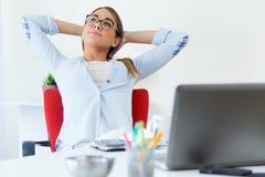 Jovem mulher bonita que relaxa um momento em seu escritório Foto de Stock Royalty Free