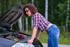 Jovem mulher bonita que repara rbroken o carro perto da estrada foto de stock