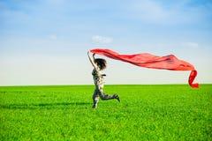 Jovem mulher bonita que salta em um prado verde Foto de Stock