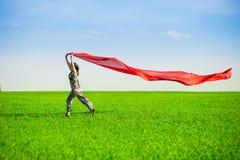 Jovem mulher bonita que salta em um prado verde Imagens de Stock Royalty Free