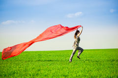 Jovem mulher bonita que salta em um prado verde Fotografia de Stock