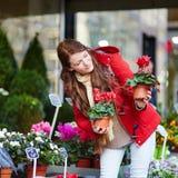 Jovem mulher bonita que seleciona flores frescas no mercado parisiense Foto de Stock Royalty Free