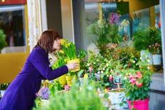 Jovem mulher bonita que seleciona flores no mercado Imagens de Stock