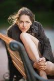 Jovem mulher bonita que senta-se em um banco fotos de stock royalty free