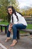 Jovem mulher que senta-se no banco imagem de stock