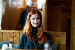 Jovem mulher bonita que senta-se em um café fotografia de stock royalty free